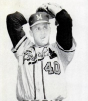 "A man wearing a baseball cap with the letter ""M"" at the centre and white baseball uniform with the words BRAVES and the number 40 across the centre, winds up and prepares to deliver a pitch"