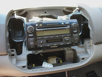 IEBus - Tear down view of dashboard with car audio head unit of Toyota Camry; OEM by JBL (logo on it)