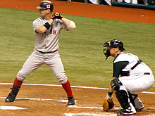A man in a grey baseball uniform stands at home plate in a left-handed batting stance.
