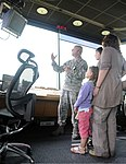 U.S. Air Force Master Sgt. Markus Fuehrmann, with the 100th Operations Support Squadron, explains air traffic control procedures to Isobel Ewing and her children during a tour at Royal Air Force Mildenhall 120810-F-UA873-026.jpg
