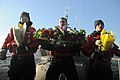U.S. Coast Guard Maritime Enforcement Specialist 2nd Class Doug Bruene, Machinery Technician 2nd Class Justin Finney and Seaman Mitch Miller prepare to cast a wreath and flowers into the water during a memorial 130112-G-ZR723-002.jpg