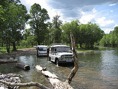 UAZ-469 towing a bus through a river in Mongolia.jpg