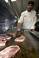 US Navy 040220-N-6204K-001 Mess Management Specialist 2nd Class Kevin Lawrence cooks pork chops on a grill in the galley aboard USS Iwo Jima (LHD 7).jpg