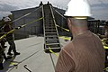US Navy 050313-N-0411D-003 Task Force Commander, Exercise New Horizons 2005, Capt. Douglas Taylor, center, hauls on a strap attached to a staircase to the roof of the Lycee Bicentenaire Universite in Gonaives, Haiti.jpg