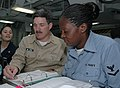 US Navy 050420-N-8623G-017 Master Chief Petty Officer of the Navy (MCPON) Terry Scott autographs an Enlisted Surface Warfare Personnel Qualification Standard manual for Yeoman 3rd Class Precious Randle.jpg