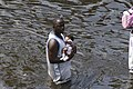US Navy 050831-N-8154G-198 A man carries a baby through the flooded streets of New Orleans outside the cities Super Dome football stadium.jpg