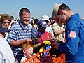 US Navy 070707-N-2888Q-003 Lt. Cmdr. Tom Winkler, a Blue Angels pilot, autographs a ballcap for a young fan following a performance at the Thunder Over Michigan Air Show.jpg