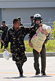 US Navy 080630-N-5961C-009 Lt. Brandon Sheets, right, carries a 100-pound sack of rice while a soldier from the Armed Forces of the Philippines lends a hand trying to keep the bag closed.jpg