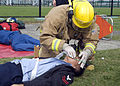 US Navy 081106-N-0483B-002 A firefighter assigned to the Commander, U.S. Naval Forces Japan (CNFJ) regional fire department places an oxygen mask on a simulated victim during a joint mass casualty exercise at Fleet Activities.jpg