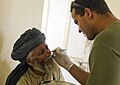 US Navy 090805-M-2581P-734 Hospital Corpsman 3rd Class Edwin Cruz, assigned to 1st Battalion, 5th Marine Regiment, treats an Afghan man with an infection on his nose.jpg