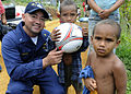 US Navy 090925-N-7478G-357 Chief Warrant Officer 3 Carlos Choto, assigned to the amphibious command ship USS Blue Ridge (LCC 19), poses with children after giving them a soccer ball during a community relations project.jpg