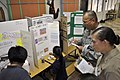 US Navy 100416-N-5539C-006 Construction Electrician 3rd Class Jill Johnston and Lt. Col. Johnny Lizama listen to third-graders from Harry S. Truman Elementary School explain their science projects.jpg