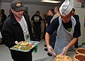 US Navy 100825-N-7642M-237 Chief Logistics Specialist (Sel.) Phillips Nguyen serves lunch to a veteran at the New England Homeless Veterans Center during chief petty officer Heritage Week, Aug. 23-Sept. 3.jpg