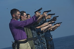 US Navy 111229-N-PB383-675 Sailors fire at their targets during a 9mm live-fire exercise aboard the amphibious transport dock ship USS New Orleans.jpg