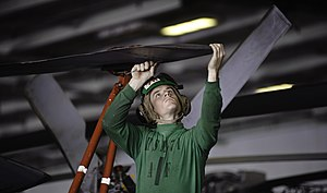 US Navy 120112-N-GC412-451 Aviation Structural Mechanic Airman Philip Alexander inspects the rotor for corrosion of an MH-60R Sea Hawk helicopter f.jpg