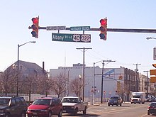 A traffic light pole with a sign on it reading Albany Boulevard U.S. Route 40/U.S. Route 322