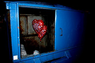 Unrequited love - A wrapped, unopened Valentines Day gift with heart-shaped helium balloons attached sits discarded in a dumpster.