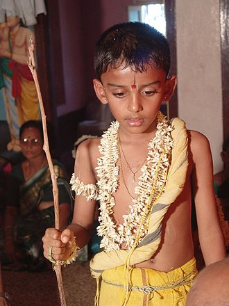 Upanayana - A boy during his upanayana ritual. The thin, yellow Yajnopavita thread runs from left shoulder to waist. Note the munja grass girdle around the waist. The peepal tree twig in his right hand marks his entry into the Brahmacharya stage of life.