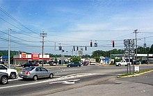 Una intersección de cinco vías señalizada de tres carreteras en un área compuesta por varios establecimientos comerciales.