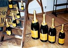 Differenti bottiglie di champagne Veuve Clicquot: da sinistra a destra, sulla scala: magnum, normale, mezza, quarto. Sul pavimento: Balthazar, Salmanazar, Mathusalem, Jeroboam.