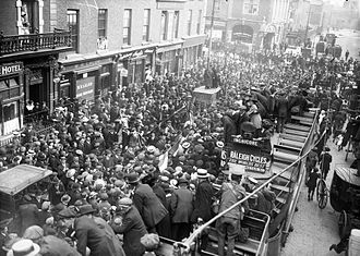Westland Row - Crowds meeting prisoners under a general amnesty, Monday, 18 June 1917. Many are on board the Dublin tramways electric trams with other spectators in the street. There are advertisements for Raleigh Cycles.