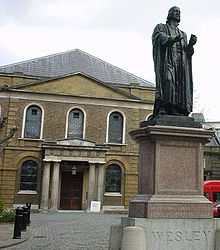 A bronze statue of John Wesley dressed in robes and preaching bands in the foreground, with a Georgian chapel in the background