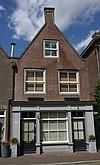 foto van Huis onder schilddak en met gepleisterde lijstgevel waarin zes en vierdelige schuiframen en een ingang met kroonlijst op pilasters
