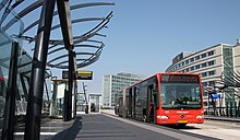 Red articulated bus at a station