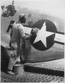 """Staff Sgt. William Accoo..., crew chief in a Negro group of the 15th U.S. Air Force, washes down the P-51 Mustang fight - NARA - 535543.tif"