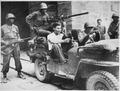 """Tricky Nazi captured. German prisoner wearing civilian clothes, sits in jeep at south gate of walled city of Lucca, Ita - NARA - 535566.tif"