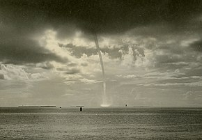 A sepia toned image of a waterspout. The waterspout extends from the dark cloud base at the top of the image to the sea below. Some spray is visible where the waterspout contacts the sea surface, and in the background, partly sunny skies are visible.