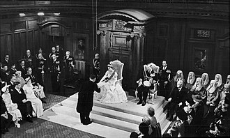 Monarchy of New Zealand - Queen Elizabeth II opening a session of the New Zealand Parliament on 12 January 1954 in the Legislative Council Chamber, Parliament House. She is accepting a vellum copy of her speech from the throne from Sir Sidney Holland (Prime Minister, 1949-1957).