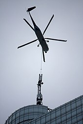 A close up view of a helicopter transporting the steeple of a building either to or from the top of the building