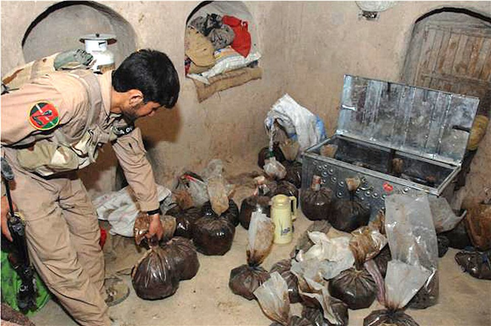 ANA soldier shows opium captured in an alleged Taliban safe house in Helmand