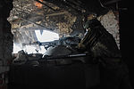 A Russia-backed armed rebel observing fighting positions though firing port at his position in ruins of International Donetsk Airport, June 12, 2015.jpg