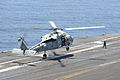 A U.S. Sailor signals an SH-60F Seahawk helicopter assigned to Helicopter Anti-submarine Squadron (HS) 5 on the flight deck of the aircraft carrier USS Dwight D. Eisenhower (CVN 69) May 25, 2013, while underway 130525-N-MD211-213.jpg