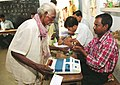A polling officer administering indelible ink to an old Saonthal (Tribal) voter before casting vote at a polling station, in Sialai village, Nanur, Birbhum district, during the Assembly Election in West Bengal.jpg