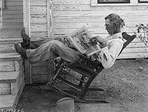 Rocking chair - A photo of man lounging in a rocking chair while reading