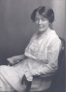 Black and white photograph of a seated woman in a white Victorian-style dress
