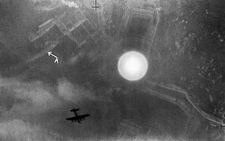 Photoflash bomb - A photoflash bomb detonates over La Spezia during an air-raid on the night of 13-14 April 1943. It has illuminated the town's dockyard and a berthed battleship (marked with an 'A'). The silhouette of one of the attacking Avro Lancaster bombers can be seen