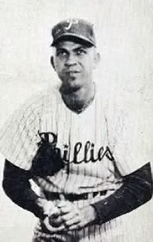 "A black-and-white photograph of a man wearing a white pinstriped baseball jersey with ""Phillies"" across the chest and a dark undershirt; he is holding a baseball in his lap with both hands and wears a baseball cap with a white ""P"" on the face atop his head"