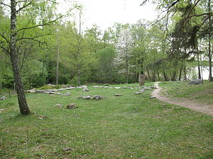 Arkils tingstad - The assembly location. To the right of the stone formation, the two runestones can be seen, and in the background there is the lake.
