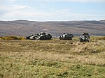 photo of armoured vehicles easy to see on bare hillside