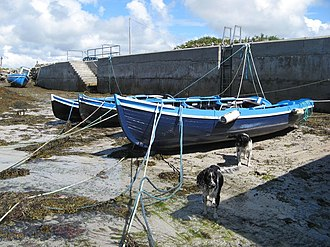Currach - A number of wooden boats in a dried-out harbour near Carna, Galway