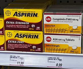 "Four boxes of medication on a store shelf above price tags. The two on the left are yellow with ""Aspirin"" in bold black type and explanatory text in English on the top box and French on the bottom. The two on the right are slightly smaller and white with the word ""Life"" in the corner inside a red circle. The text, in French on top and English below, describes the medication as ""acetylsalicylic acid tablets"""
