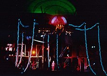 An image of a stage with a giant luminescent spider overhead, its body glowing green, its head glowing red and its legs glowing blue. Below the spider, tiny human forms can be see on stage