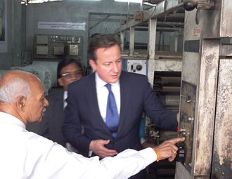 Uthayan - David Cameron, Prime Minister of the United Kingdom inspecting burnt down printing press of Uthayan newspaper in Jaffna on 15 November 2013 while M. V. Kanamaylnathan, the Editor of the newspaper explaining something to him. E. Saravanapavan, the Managing Director of the newspaper looking on.