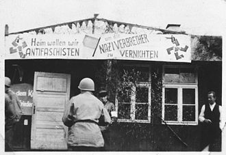 """Buchenwald Resistance - Anti-nazi banner outside a barrack at Buchenwald. The sign, in rhyme, says """"We anti-fascists want to go home to eradicate Nazi criminals""""."""
