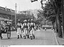 Dans une artère de Bombay en 1932, marins britanniques patrouillant en armes pour assurer l'ordre public.