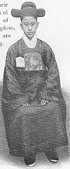 This picture is of a boy in a robe, white scarf, running shoes, and t-shaped hat. He is sitting with a tote bag on his lap. The tote bag is the same color as his robe. There is a folder sticking out of the bag with the picture of a lion or a poodle on it.